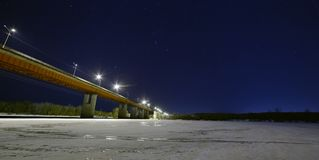 Stars in the night sky above illuminated car bridge. royalty free stock images