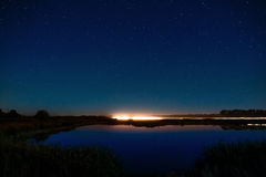 The stars in the night sky reflected in the river. The lights fr Royalty Free Stock Photography