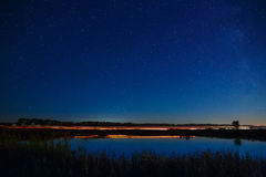 The stars in the night sky reflected in the river. The lights fr Royalty Free Stock Images