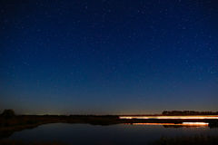 The stars in the night sky reflected in the river. The lights fr Royalty Free Stock Photo