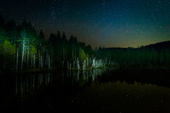 Stars in the night sky reflecting in Deception Pond at night, in Stock Image