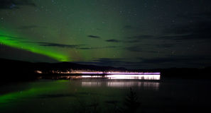 Stars and Northern Lights over dark Road at Lake Royalty Free Stock Images
