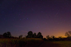 Stars over the forest and village lights in right corner Stock Photo