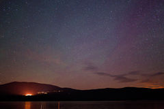 Stars over a mountain lake Stock Photography