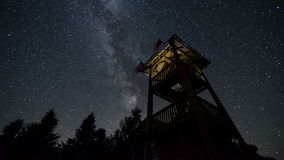 Stars sky with milky way turning over lookout tower time lapse. Astronomy starry night. 4K. Timelapse video of beautiful summer night with millions stars stock video