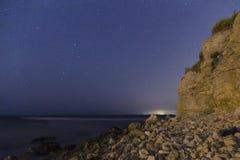 Stars in sky over rocky beach Royalty Free Stock Photo