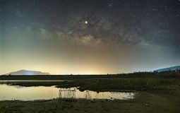 The stars in the sky reflect the light at night. The Milky Way above the mountains and the pond. Mae Prachan Dam and Reservoir, Phetchaburi, Thailand royalty free stock photo