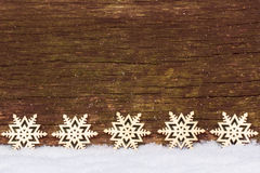 Stars in the snow in front of wood Royalty Free Stock Photography