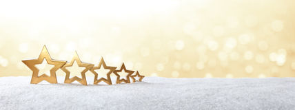 5 stars snow gold banner. Five golden stars on snow in front of bright yellow light, christmas background, copy space, panorama format Stock Photos