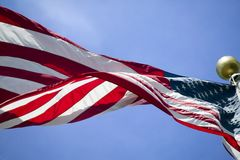 Stars and Stripes. The American flag, the stars and stripes flies strong in the wind against a blue sky Stock Image
