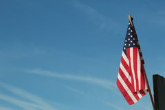 Stars and stripes against blue sky. American flag on a stick reaching towards a blue sky Royalty Free Stock Photo
