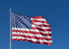The stars and stripes of the American flag against a deep blue sky. A red, white and blue American flag with stars and stripes unfurled in the wind Stock Photography