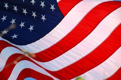 American Flag. The stars and stripes of the American flag wave and flutter patriotically in the afternoon sun Royalty Free Stock Photo