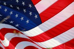American Flag. The stars and stripes of the American flag wave and flutter patriotically in the afternoon sun Stock Images