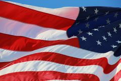 American Flag. The stars and stripes of the American flag wave and flutter patriotically in the afternoon sun Royalty Free Stock Image
