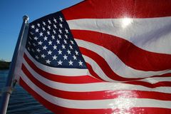 American Flag Backlit on Lake. The stars and stripes of the American flag wave and flutter patriotically backlit by the evening sun next to a lake Royalty Free Stock Image