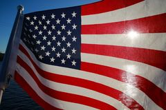 American Flag Backlit. The stars and stripes of the American flag wave and flutter patriotically backlit by the evening sun next to a lake Royalty Free Stock Image