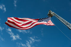 Stars and Stripes - Boom. Large American flag flies from fire department hydraulic boom against brilliant blue sky Stock Photos