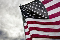 American Flag Stars and Stripes Flying. American flag right justified unfurled against a cloudy sky Royalty Free Stock Image