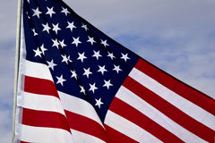Stars and Stripes Flying. American flag right justified unfurled against a cloudy sky Royalty Free Stock Photo
