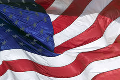 The stars and stripes, and red, white and blue colors of a US Flag blow in the wind. Royalty Free Stock Image