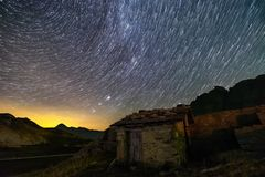 Stars trails and isolated house in switzerland alps. Mountain stock photos