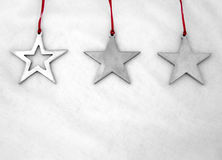 Stars on White. Three star-shaped, silver ornaments on red ribbons Stock Photo