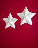 Stars. White paper stars hanging with string on a red background. Copy Space royalty free stock photo