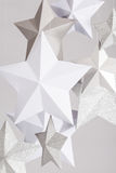 Stars. White, silver and pearl paper stars hanging with string on a grey background stock photo