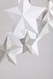 Stars. White, silver and pearl paper stars hanging with string on a grey background. Copy space stock photography