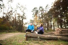 Starsi biegacze siedzi na drewnianych belach, odpoczywa, woda pitna Fotografia Stock