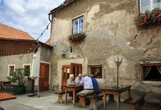 Starsi ludzi siedzi przy stołem w ulicznej restauraci Weissenkirchen w dera Wachau, Austria zdjęcia royalty free