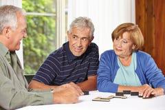 Starsi ludzie bawić się domino Fotografia Royalty Free