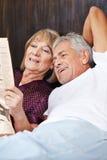 Starsi ludzie czyta gazetę w łóżku Obraz Stock