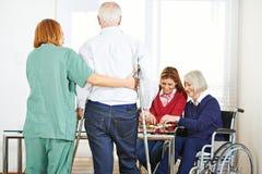 Starsi ludzie w karmiącym domu z garegiver Zdjęcie Royalty Free