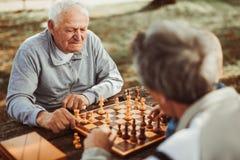 Starsi mężczyzna ma zabawę i bawić się szachy fotografia stock