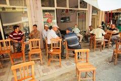 Starsi mężczyzna siedzi wokoło stołów i opowiada w nieociosanej kawiarni wioska Zdjęcia Stock