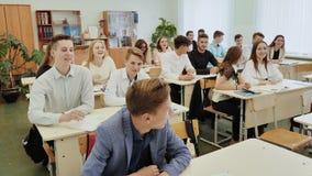 Starsi ucznie bawić się gemowego bieg wokoło ich klasy i siedzą puszek przy ich biurkami przed lekcją zbiory