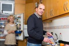 Starsi współmałżonkowie przy nowożytną kuchnią Obrazy Royalty Free