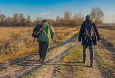 Starsi wycieczkowicze chodzi na wiejskiej drodze z plecakami Obraz Royalty Free