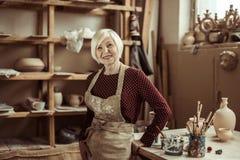 Starsza żeńska garncarka w fartuch pozyci przy warsztatem fotografia royalty free