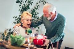 Starsza żeńska osoba z zadowoloną twarzą bierze teraźniejszości pudełko obraz royalty free