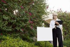 Starsza agent nieruchomości pozycja znak deski czytaniem od schowka Zdjęcie Stock