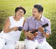 Starsza Azjatycka para bawić się muzykę w parku obraz stock