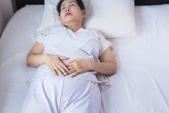 Starsza azjatykcia kobieta ma bolesnego stomachache na sypialni, Żeński cierpienie od brzusznego bólu podczas gdy kłamający w syp fotografia royalty free