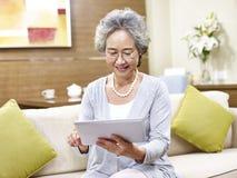 Starsza azjatykcia kobieta używa pastylka komputer zdjęcie stock