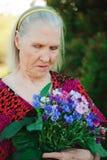 Starsza babcia z bukietem kwiaty w parku zdjęcie stock