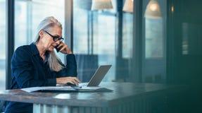 Starsza biznesowa kobieta opowiada na telefonie komórkowym obraz stock