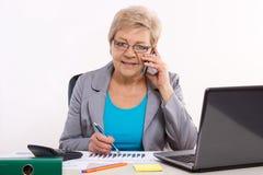 Starsza biznesowa kobieta opowiada na telefonie komórkowym i działaniu przy jej biurkiem w biurze, biznesowy pojęcie obraz royalty free