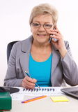 Starsza biznesowa kobieta opowiada na telefonie komórkowym i działaniu przy jej biurkiem w biurze, biznesowy pojęcie zdjęcie royalty free